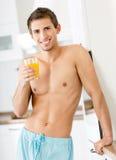 Halva-naken man med exponeringsglas av fruktsaft royaltyfri fotografi