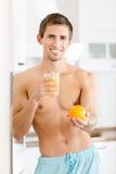 Halva-naken man med exponeringsglas av fruktsaft och apelsinen Fotografering för Bildbyråer