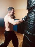 Halva-naken manboxning som stansar påsen i sportidrottshall arkivbild