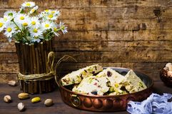 Halva with pistachio on a wooden table. Halva with pistachio on a rustic wooden table Royalty Free Stock Photography
