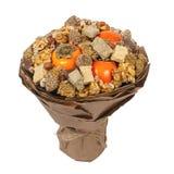 Halva, ruptures de sésame, écrous, chocolats et kakis, décorés sous forme de bouquet de cadeau sur un fond blanc image stock