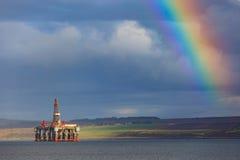 Halva sänkbara oljeplattformar och regnbåge på den Cromarty firthen Arkivfoton