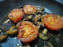 Halva skivade tomater som steker med organiska champinjoner Fotografering för Bildbyråer