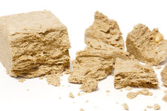 Halva subsolar on a white background. Halva, crumbled into pieces on a white background Stock Photography
