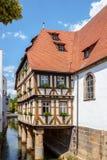 Halva timrat hus på en flod i Forchheim Fotografering för Bildbyråer