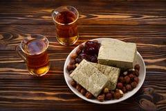 Halva z herbatą, dokrętki, wysuszone owoc na drewnianym stole obraz royalty free