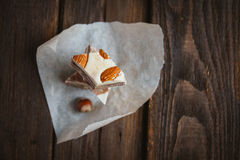 Halvah on a brown background. Pieces of Turkish halva with nuts on brown background Stock Photos