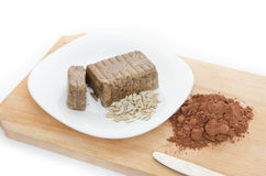 Halvah with cocoa powder on wood plank Stock Photography