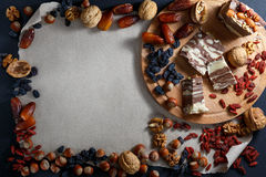 Halvah, nuts and dried fruit on paper background. Four pieces of striped halva on a wooden board. Nuts and dried fruit on paper. Directly above. Place for an stock photos