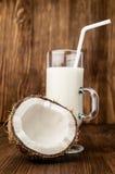Halvan av den nya kokosnöten och kokosnöten mjölkar i ett exponeringsglas royaltyfri bild