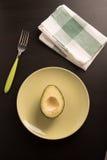 Halvan av mogen avokadofrukt without kärnar ur i en platta Royaltyfria Foton