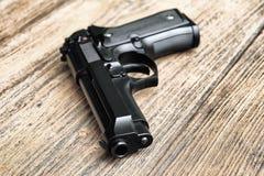 Halvautomatisk handeldvapen som ligger på träbakgrund , 9mm pistol Royaltyfri Fotografi
