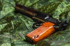 Halvautomatisk tystad pistol på PIXELkamouflagebakgrund Royaltyfria Foton