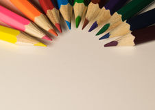 Halvcirkel av kulöra blyertspennor på vit bakgrund Arkivfoto
