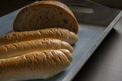 Halve brood en broodjes op de blauwe houten plaat Stock Afbeeldingen