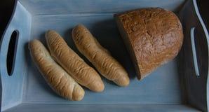 Halve brood en broodjes op de blauwe houten plaat Stock Foto's
