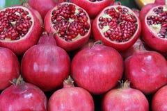 Halve Granaatappels met zaden bij de marktkraamachtergrond stock foto
