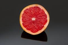 Halve grapefruit on dark shiny surface with reflection Stock Photo
