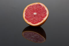 Halve grapefruit on dark shiny surface Stock Photography