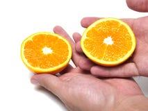 Halve sinaasappel in de hand Stock Fotografie