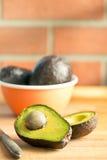 Halved avocado on kitchen table Royalty Free Stock Photo