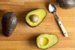 Halved avocado on kitchen table Stock Photo