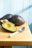 Halved avocado on kitchen table Royalty Free Stock Photos