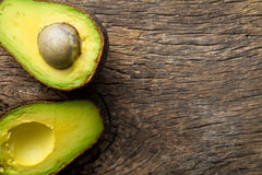 Halved avocado on old table Royalty Free Stock Photos