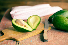 Halved avocados on old wooden table Stock Photo