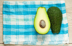 Halved avocados on rustic wooden background Stock Photo