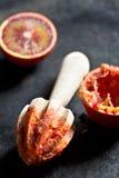 Halved blood orange and juicer Stock Photos