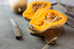 Halved butternut squash pumpkin on wood cutting board. Knife and kitchen towel on dark concrete stone background. Low angle shot Royalty Free Stock Photo