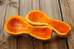 Halved butternut squash on wooden background Stock Images