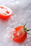 Halved cherry tomato on sea rock salt Stock Photography