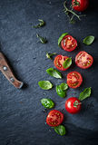 Halved cherry tomatoes and basil leaves Royalty Free Stock Photos