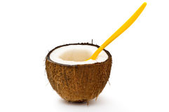 Halved coconut with orange spoon Royalty Free Stock Image