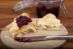 Halved croissant with cherry marmalade on wooden plate Stock Photos