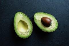 Halved fresh avocado on slate Royalty Free Stock Photos