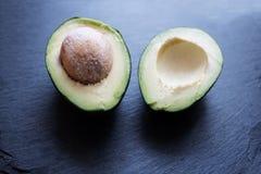 Halved fresh avocado on slate Stock Photo