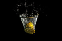 Halved fresh lemon splashing into clean water Stock Photography