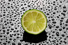 Halved fresh lime on a wet black background. Overhead view of a halved fresh lime with pulp detail on a wet black background with water droplet pattern and stock photos