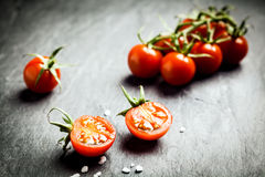 Halved fresh ripe grape tomato. Showing the pips and juicy pulp in the foreground with a bunch of tomatoes on the vine behind on a dark rustic table, low angle royalty free stock photography