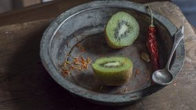 Halved kiwi fruit with red chili in weathered copper bowl. Split up kiwi fruit on wooden surface with weathered copper bowl on black background Stock Images