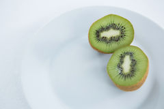 Halved kiwis in plate on white background. Close-up of halved kiwis in plate on white background stock photo