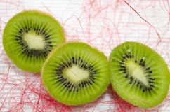Halved kiwis on a white cardboard. Decorated with pink straw stock image