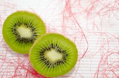 Halved kiwis on a white cardboard. Decorated with pink straw stock images