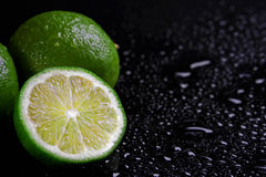 Halved lime on a wet black background. Halved and whole tangy limes on a wet black background with copyspace used in cooking as a flavouring and for its aromatic royalty free stock photography