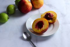 Halved nectarine on white plate stock photography