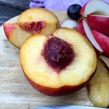Halved nectarine on a wooden plate Stock Photography