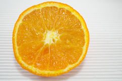 Halved orange on a white cardboard close up Stock Image
